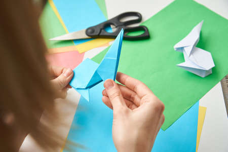 DIY concept. Woman make origami easter rabbit from color paper. Origami lessons Zdjęcie Seryjne