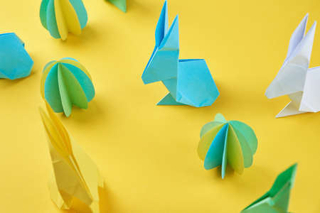 Paper origami Esater rabbits and colored eggs on yellow background. Easter celebration concept Zdjęcie Seryjne