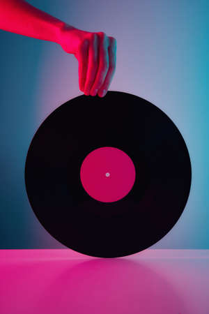 Hand hold retro vinyl disc with neon lights. Vintage music background Zdjęcie Seryjne