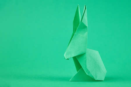 Paper origami Esater rabbit on a green background. Easter celebration concept