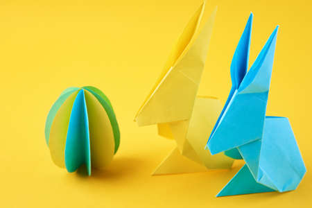 Two paper origami Esater rabbits and colored egg on yellow background. Easter celebration concept