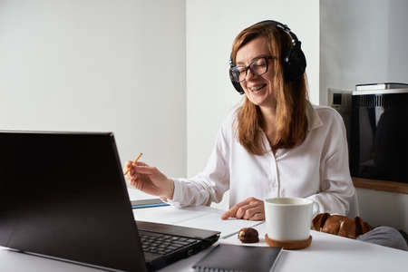 Remote work. Online course, distance education and e learning concept. Woman in headphones listen audio course at laptop and make marks in notebook