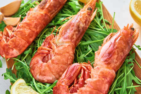 Red raw prawns, close up. Fresh shrimps with lemon and rucola. Seafood background Zdjęcie Seryjne
