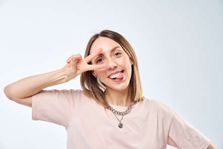 Positive woman portrait. Cheerful happy young woman smiling and show victory gesture on a white background