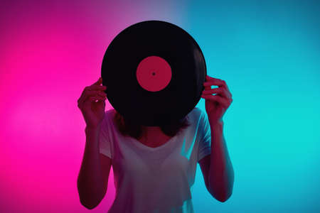 Woman hold retro vinyl disc with neon light