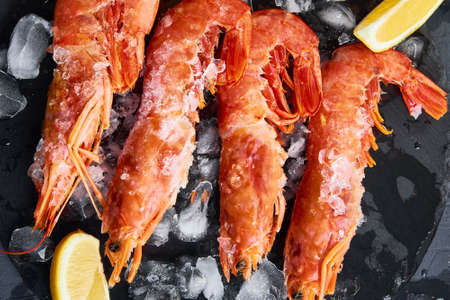 Frozen seafood. Fresh shrimps with lemon on dark background. Red raw prawns Stock Photo