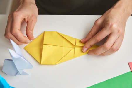 DIY concept. Woman make origami easter rabbit from color paper. Origami lessons Stock Photo