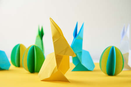 Paper origami Esater rabbits and colored eggs on a yellow background. Easter celebration concept
