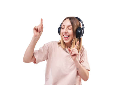 Happy smiling woman with headphones listening music and dancing
