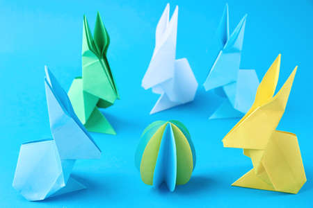 Paper origami Esater rabbits and colored eggs on a blue background. Easter celebration concept