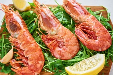 Red raw prawns, close up. Fresh shrimps with lemon and rucola. Seafood background Stock Photo