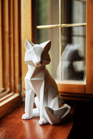 Polygonal geometric animal on windowsill near window Stock Photo