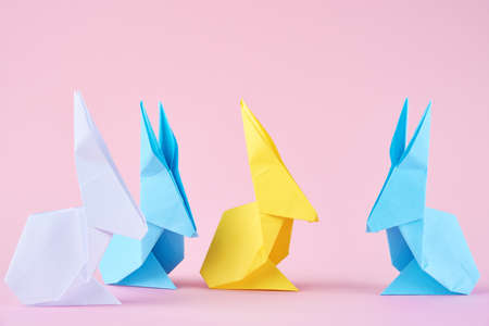 Paper colorful origami Esater rabbits on a pink background. Easter celebration concept Banco de Imagens