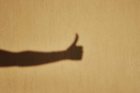 Thumb up gesture shadow on wall Banco de Imagens