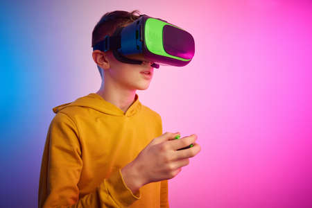 Boy with virtual reality glasses on colorful background. Future technology, VR concept Stock Photo