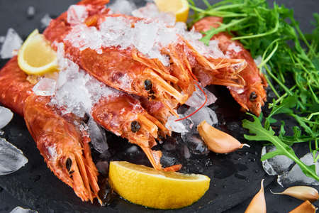 Seafood background. Fresh shrimps with lemon on dark background. Red raw prawns