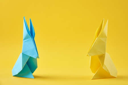 Two paper colorful origami Esater rabbits on a yellow background. Easter celebration concept Stock Photo