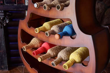 Colorful wine bottles wrapped in a rope on stand. Interior design element