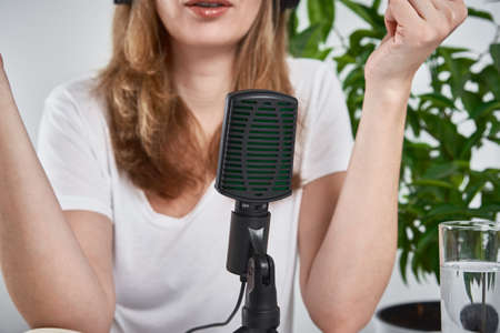 Woman recording online podcast at home. Microphone on table. home studio workplace