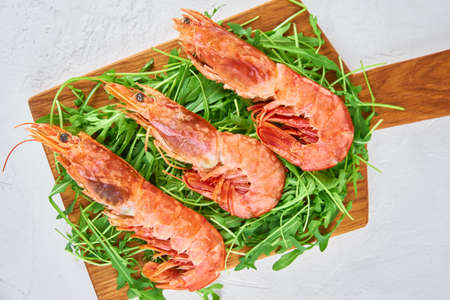 Red raw prawns, close up. Fresh shrimps with rucola. Seafood background Stock Photo