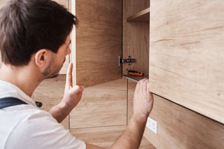 Man open kitchen cupboard. Repairman in uniform fixing cabinet at kitchen Stock Photo