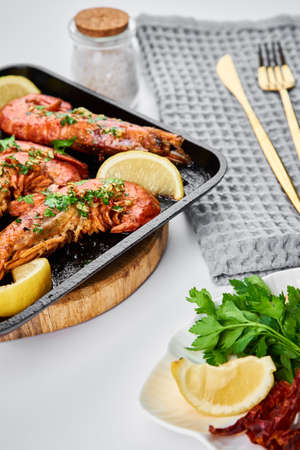 Grilled large queen shrimps with lemon and spices on the grill pan