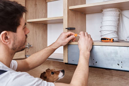 Man fixing wire in kitchen cabinet with dog Stock Photo