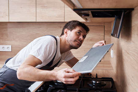 Man repairs hood in kitchen. Replacement filter in cooker hood Stock Photo