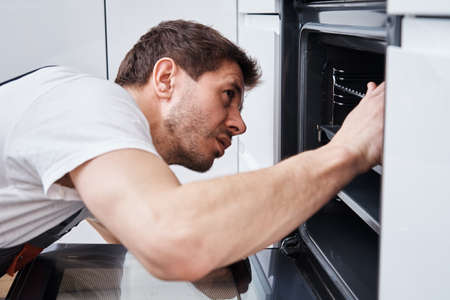 Man fixing problem in the oven in kitchen