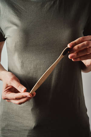 Woman in green t-short holds bamboo toothbrush. Eco friendly items and zero waste concept