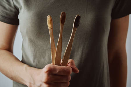 Woman in green t-short holds bamboo toothbrushes. Eco friendly items and zero waste concept