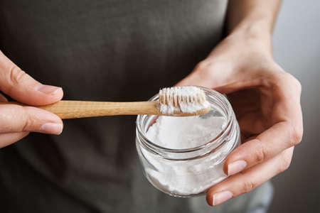 Woman holds bamboo toothbrush and tooth powder. Zero waste and ecological products concept