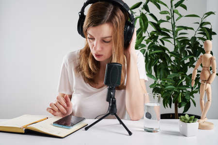 Woman in headphones have online lessons at home. E-learning and podcast concept