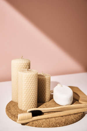 Bamboo toothbrushes and candles on pink background. Reuse natural products Archivio Fotografico
