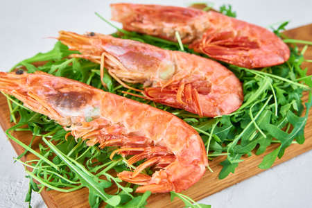 Fresh shrimps with rucola. Red raw prawns, close up. Seafood background