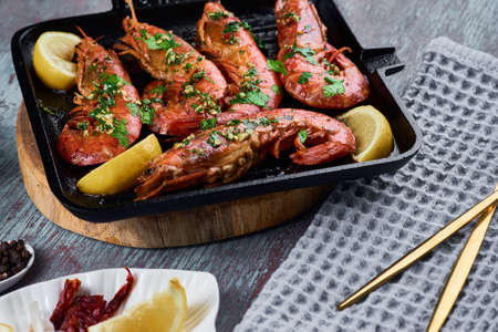 Grilled large queen shrimps with lemon and spices on grill pan