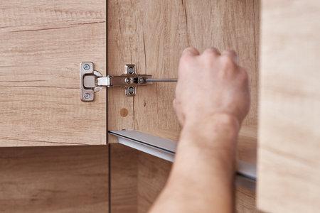 Srewdriver fixing kitchen cabinet door, close up