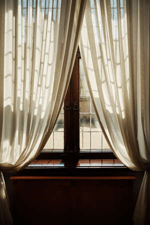 Old window with white curtains and shining rays of the sun
