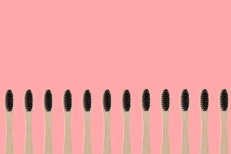 Row of eco friendly reusable bamboo toothbrushes on pink background, top view with copy space. Zero waste and organic items concept