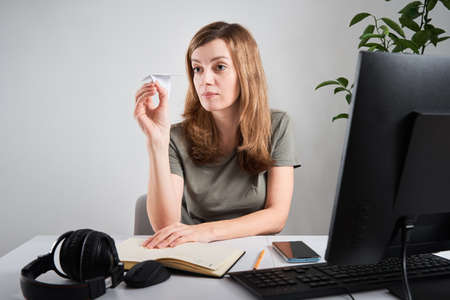 Woman launches paper plane and dreaming about vacation while sitting at computer at remote work Archivio Fotografico