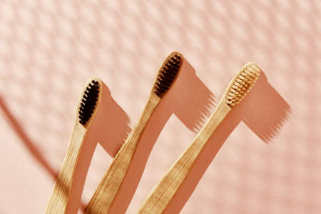 Eco friendly bamboo toothbrushes on pink background. Flat lay top view.