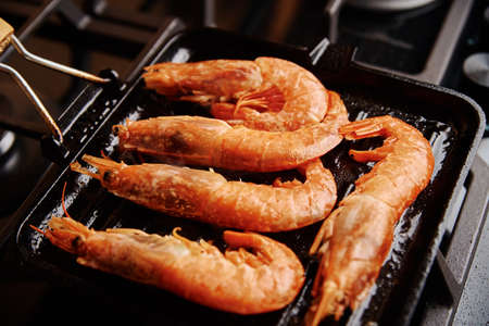 Grilled large shrimps with lemon and spices on grill pan