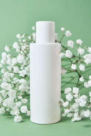 Beaty product package. Cosmetic bottle on pastel green background with plant leaves. Cosmetics mock up