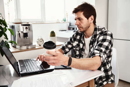 Man working at home office with laptop and smartphone. Online business concept. Remote work