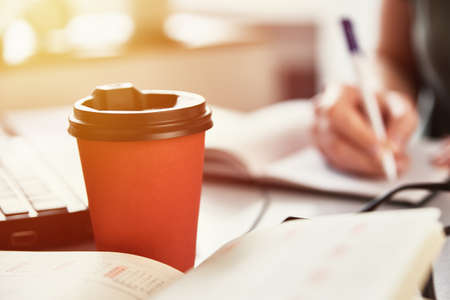 Remote work concept. Red coffee cup on the workplace. Freelancer work at home