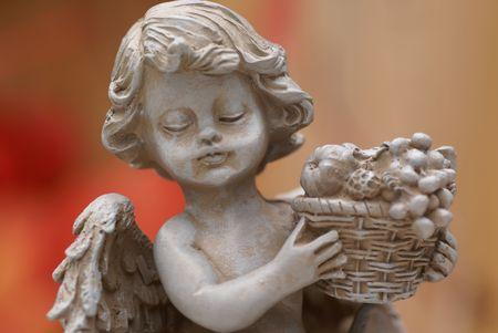 fruitmand: Little Angel standbeeld met fruitmand. Stockfoto
