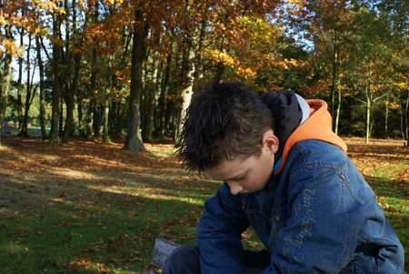 Sad young boy sitting in the park. Stock Photo - 1935668