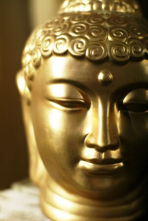 buddha face: The head of a golden buddha in a warm (atmos)sphere. Stock Photo