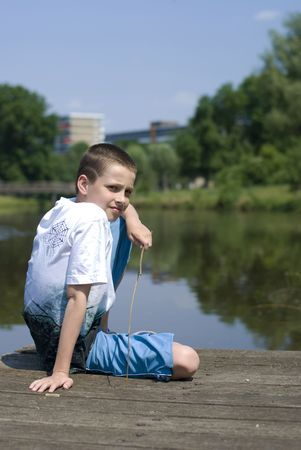 bore: Boy sitting on a dock, looking a bit bored.