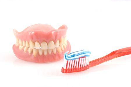 molares: Dentadura postiza y cepillo de dientes con pasta de dientes aislados en blanco.  Foto de archivo
